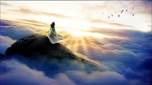 girl, on cloud draped mountain gazing into radiant sunrays